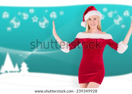 Festive blonde smiling at camera against blurred christmas frame