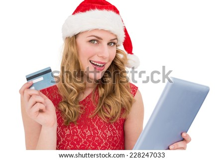 Festive blonde woman using her credit card and tablet pc on white background