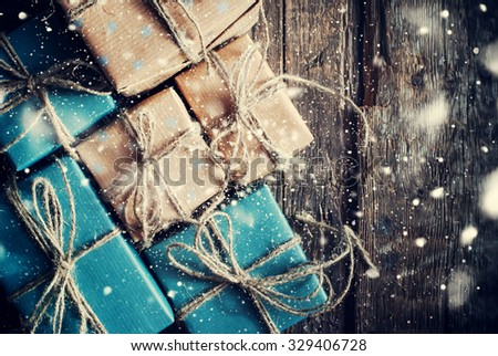 Festive Boxes with Linen Cord. Natural Gifts on Wooden Background. Drawn Snowfall - stock photo