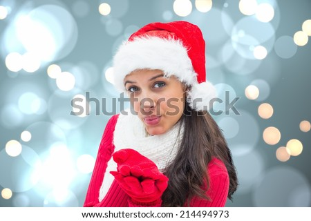Festive brunette blowing against white glowing dots on blue