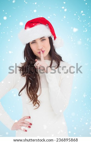 Festive brunette in santa hat keeping a secret against blue background with vignette - stock photo