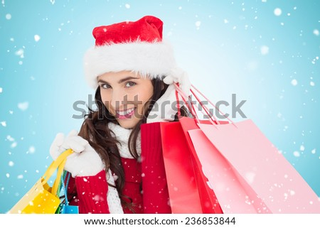Festive brunette in winter wear holding shopping bags against blue vignette - stock photo