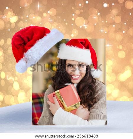 Festive brunette pressing gift at christmas against yellow abstract light spot design - stock photo