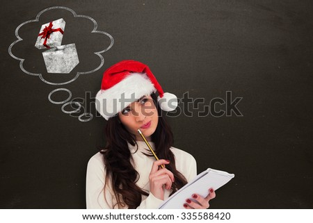 Festive brunette thinking about her christmas list against blackboard - stock photo