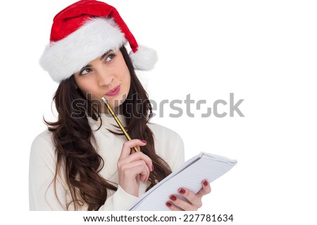 Festive brunette thinking about her christmas list on white background - stock photo