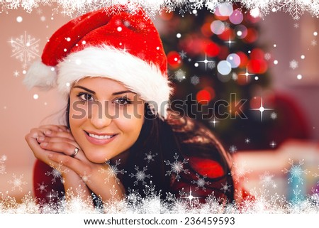 Festive brunette wearing a santa hat against fir tree forest and snowflakes
