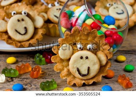 Festive cake shaped monkey face close-up on the wooden background with colored sweets. Treats at the children's party. Selective focus.
