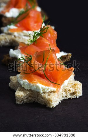 Festive canapes in star shape with smoked salmon on cream cheese with dill garnish in a row on dark brown wood, for christmas time or new year, vertical,