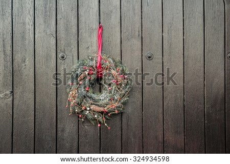 Festive Christmas Advent wreath is hanging outside at brown wooden gates background - stock photo