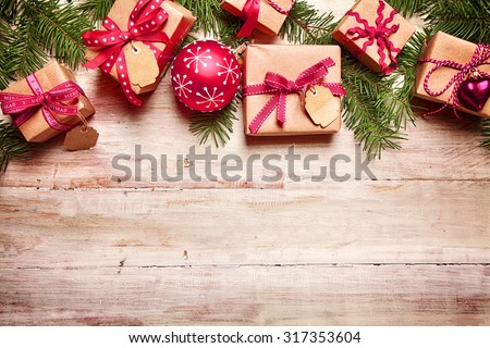 Festive Christmas border with gifts tied with red ribbon, matching red baubles and fresh pine foliage over rustic wood with copyspace for your seasonal greeting - stock photo
