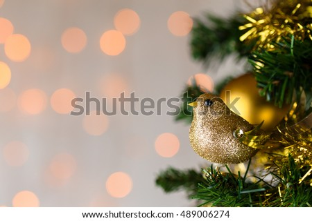 Festive Christmas close up of tree decorated with gold glitter robin, tinsel and bauble. Bokeh copy space.