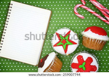 Festive Christmas cupcakes and blank cookbook page on green background  - stock photo