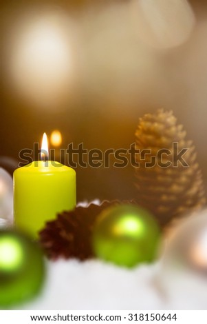 Festive christmas decoration in green, lightning candles, fir cones and snow on the ground - stock photo