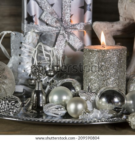 Festive christmas decoration in silver with burning advent candles. - stock photo