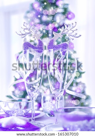 Festive Christmas dinner at home, evergreen tree with purple decoration, shiny reindeer toys decorate wineglasses, happy holidays concept