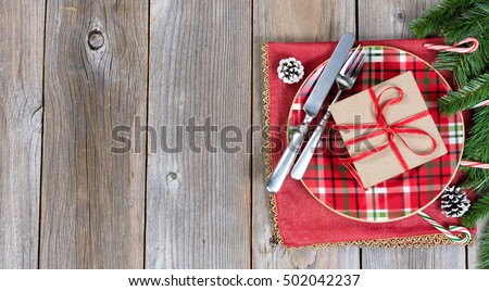Festive Christmas dinner setting with evergreen branches and gift on top of rustic wood. Top view with copy space.