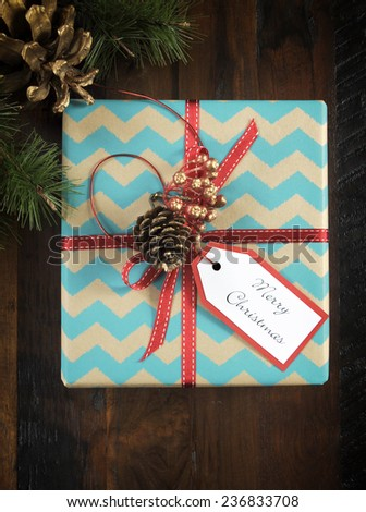 Festive Christmas gift box with chevron stripe wrapping on dark recycled wood table. Vertical. - stock photo