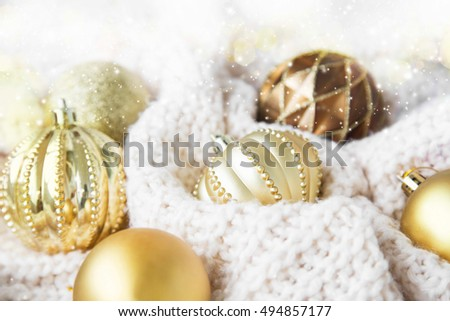 Festive Christmas golden globes with lights and sparkle on white fluffy woolen blanket