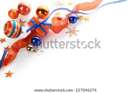 Festive Christmas greeting card background with a corner arrangement of orange, gold and blue decorations, baubles, gift and ribbon over white with copyspace - stock photo