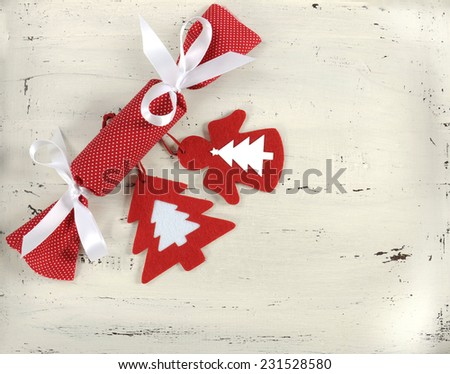 Festive Christmas Holiday background with red and white theme handmade fabric bon-bon cracker with felt decorations on vintage shabby chic white wood background. - stock photo