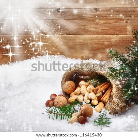 Festive christmas nuts and spices tumbling from a burlap bag onto fresh winter snow with sunlight catching twinkling falling snowflakes and copysapce - stock photo