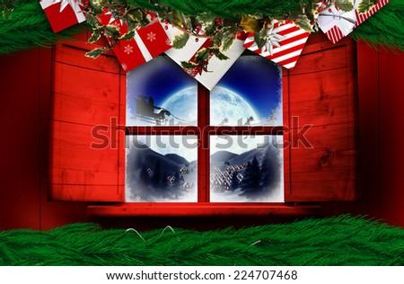 Festive christmas wreath against santa delivery presents to village - stock photo