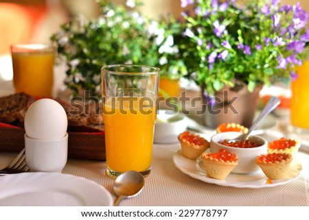 Festive continental breakfast with red caviar, soft-boiled egg and orange juice. Table decorated with a bouquet of bells flowers. Sunny light.