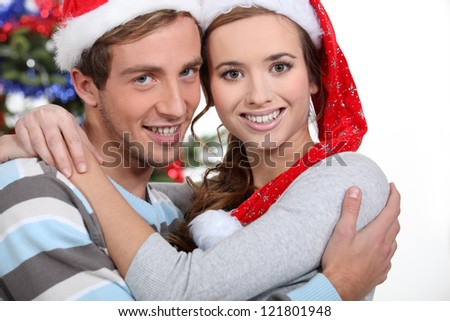 Festive couple hugging by the Christmas tree - stock photo