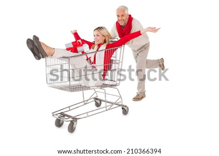 Festive couple messing about in shopping trolley on white background