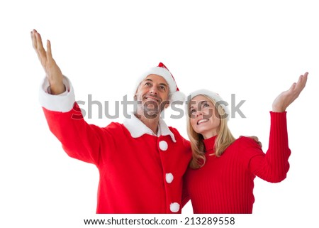 Festive couple standing with arms raised on white background