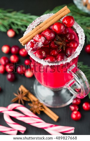 Festive Cranberry drink on Christmas background with fir branches and fresh berries, selective focus. Holiday concept. Dark stone table, Winter time