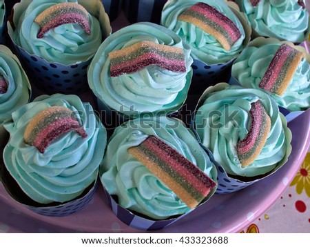 Festive creative Teal birthday cupcake with butter cream icing and colorful decoration - stock photo