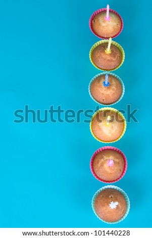Festive cupcakes with candles on gradient background,top view - stock photo