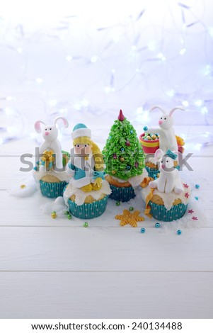 Festive cupcakes with sugar figures on a bright lights background vertical format. Snow Maiden and rabbits decorating the Christmas tree.  - stock photo