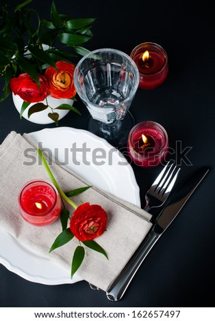 Festive dining table setting with red buttercup flowers, candles, napkins and shiny new cutlery on a black background
