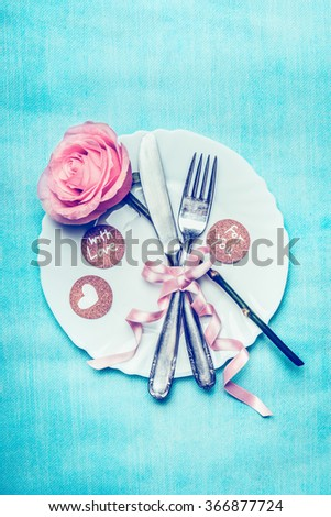 Festive dinner table place setting with rose, ribbon decoration and love message cards on blue pale background, top view. Retro color toned - stock photo