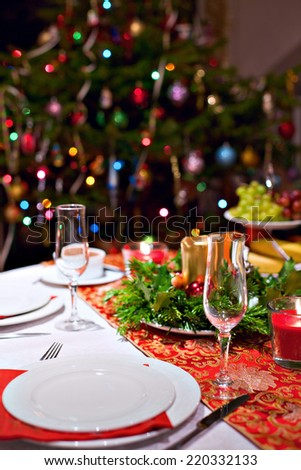 Festive dinner table setting with red table cloth, champagne glasses, candles and Christmas tree on the background