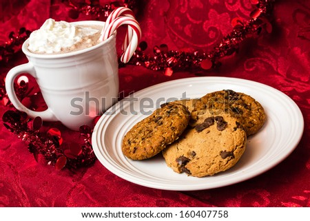 Festive display of cookies and hot chocolate for Santa on red background - stock photo