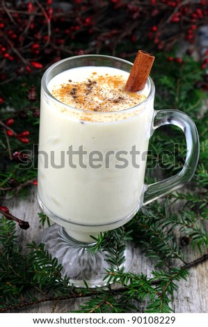 Festive eggnog with green boughs and red berries - stock photo
