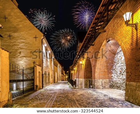 Festive European town; nocturnal view from calm medieval street - stock photo