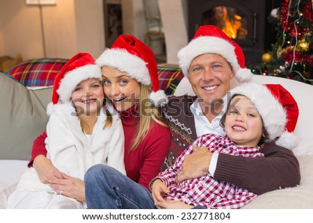 Festive family in santa hat hugging on couch at home in the living room - stock photo