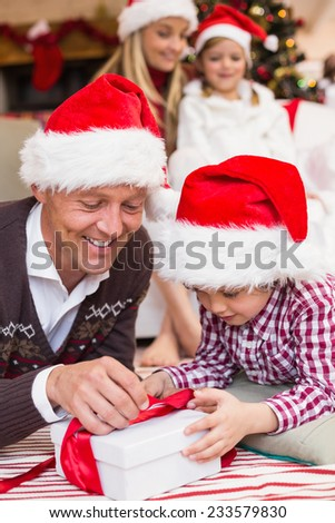 Festive father and son opening christmas present at home in the living room - stock photo