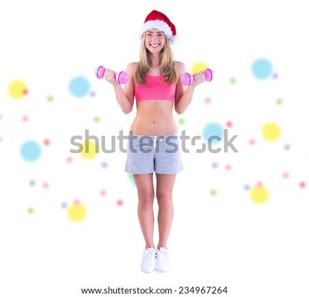 Festive fit blonde holding dumbbells against dot pattern - stock photo