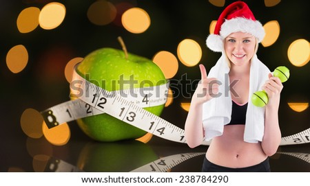 Festive fit blonde smiling at camera against measuring tape - stock photo