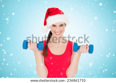 Festive fit brunette holding dumbbells against blue vignette - stock photo