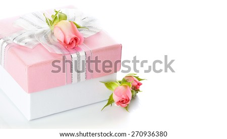 Festive gift box with a silver bow and pink roses. Elegant gift. - stock photo