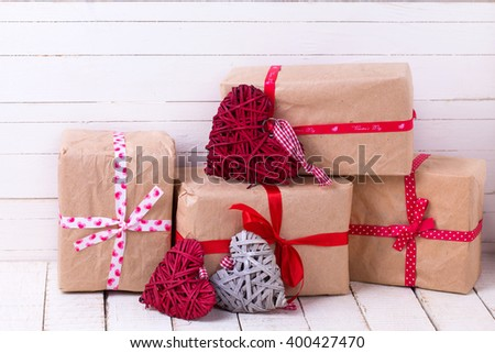 Festive gift boxes and  grey and red decorative hearts  on white wooden background. Selective focus. - stock photo