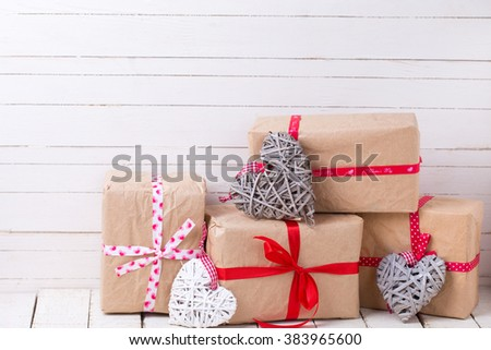 Festive gift boxes and  grey and white decorative hearts  on white wooden background. Selective focus. Place for text.  - stock photo