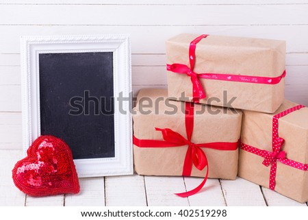 Festive gift boxes, decorative heart  and empty blackboard on white wooden background. Selective focus. Place for text. - stock photo