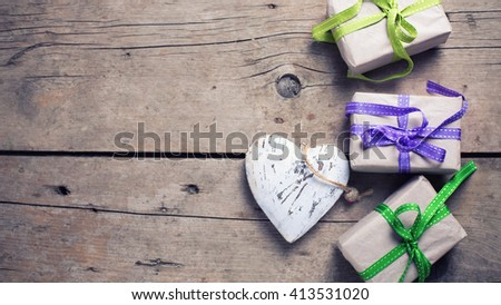 Festive gift boxes with presents and  rustic decorative heart on aged wooden background. Selective focus. Place for text. Toned image. - stock photo